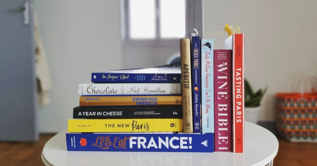stack of books about French food and culture, including cookbooks and books on wine.